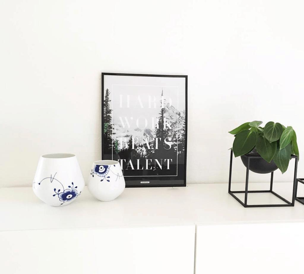 Hard Work i sort billederamme med Royal Copenhaven vase og Kubus skål på hvide skabe