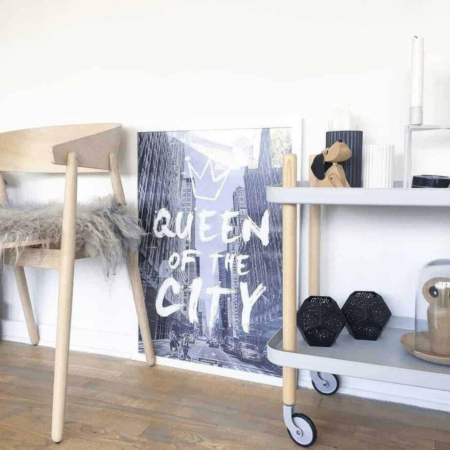 Stor plakat med tekst i hvid billederamme ved siden af stol og rullebord med design interiør