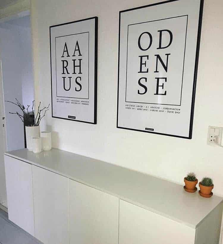 To by plakater med Århus og Odense hængende på hvid væg over tre skabe med hvide lyngbyvaser