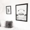 Stor lys plakat i tyk mørk billederamme ved siden af lille lys plakat i sort billedramme på væggen