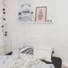 Lys plakat i soveværelset i hvid billederamme på hylde over sengen