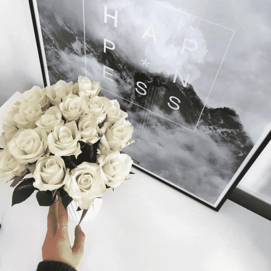 Lys plakat i sort billederamme med lyngbyvase og lyse blomster