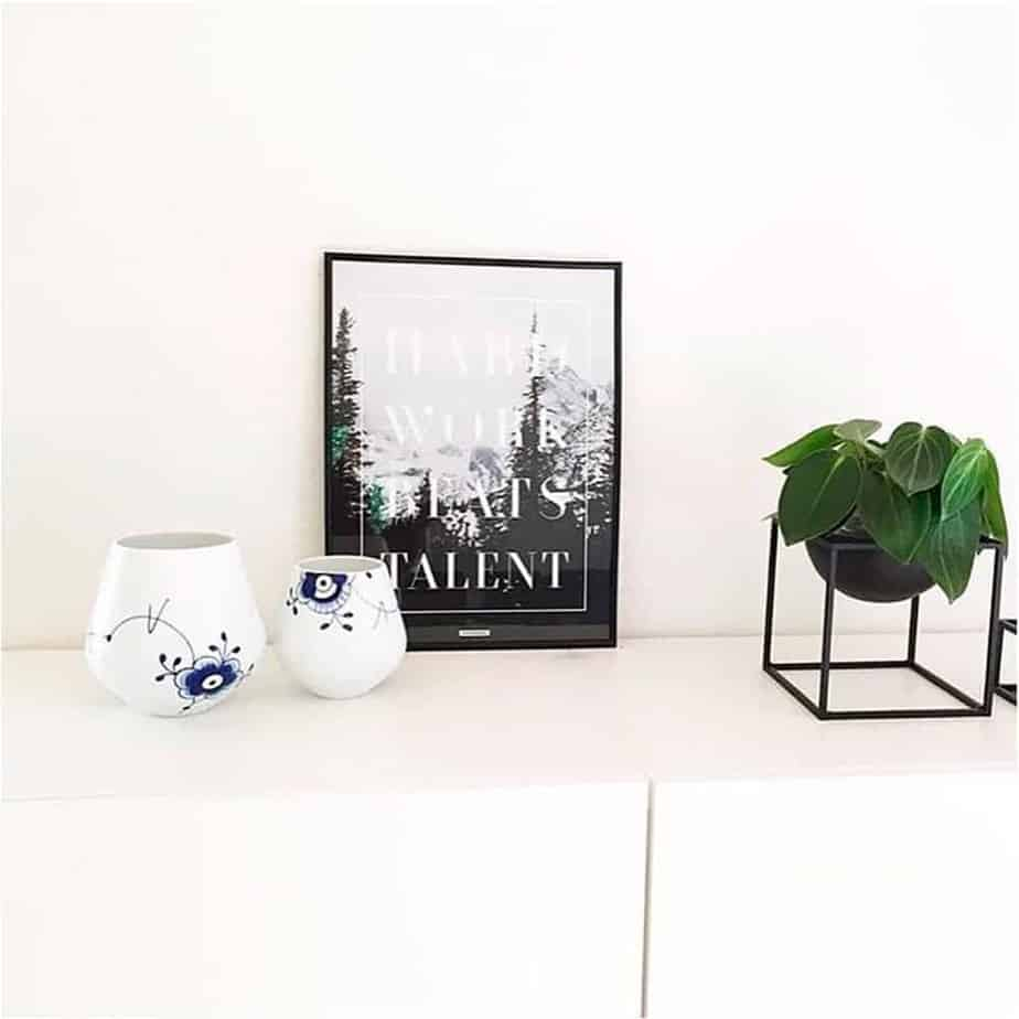 Lys plakat med motiverende tekst ved vase og stueplante