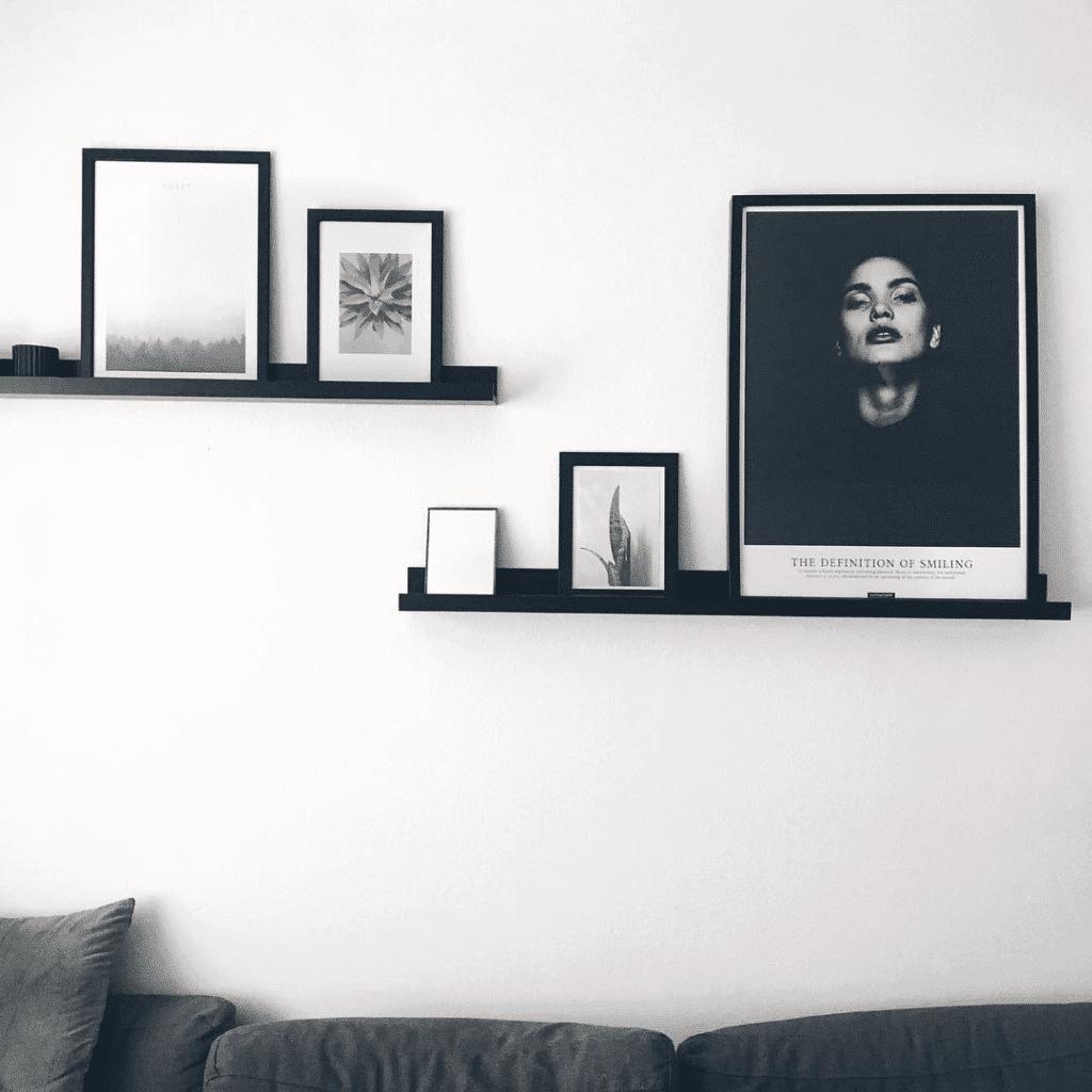 Sort hvid plakat på sort træ hylde over sofaen