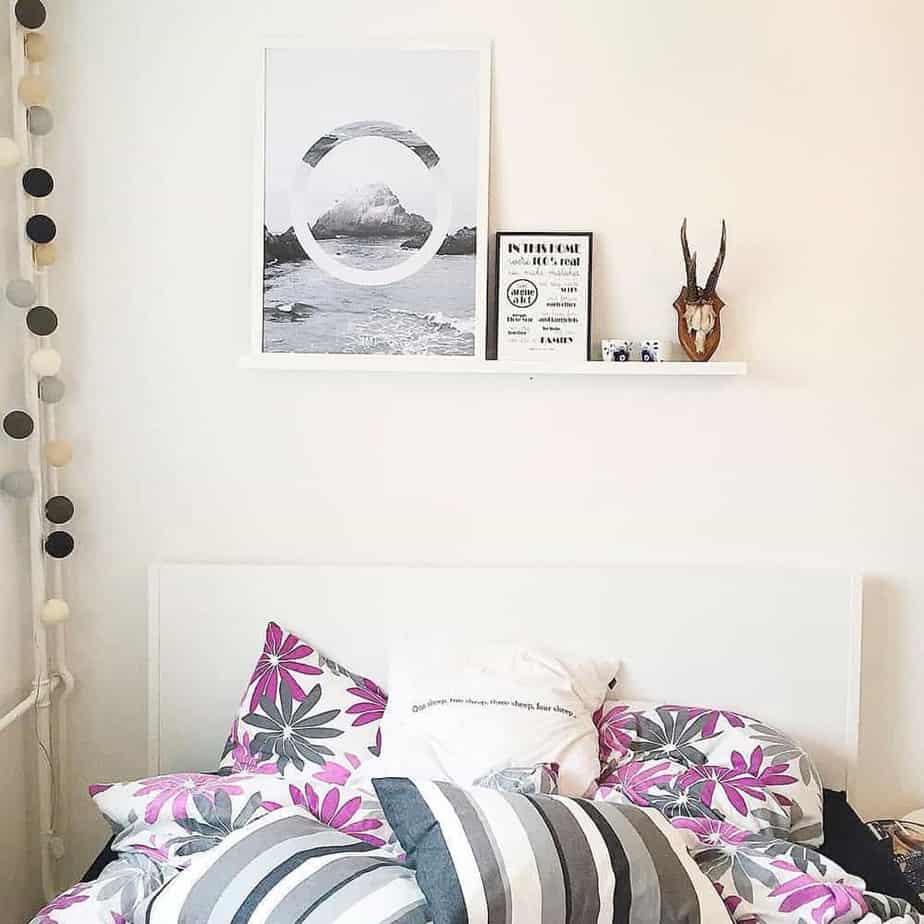 Lys plakat på hylde over seng i sofaværelse