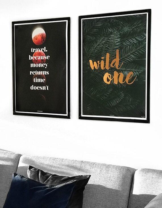 Matchende plakatsæt med TRAVEL plakat og WILD ONE plakat i stuen over sofaen i sorte aluminium rammer